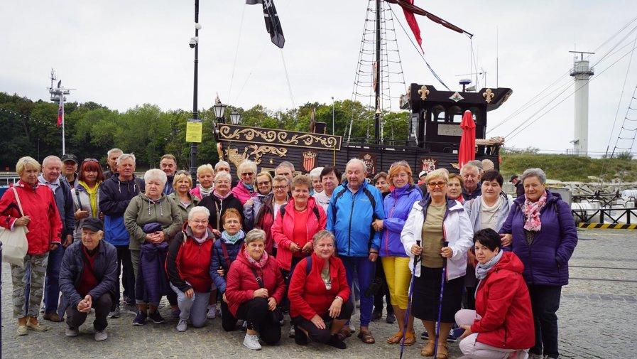 Kolejne kilometry na wybrzeżu pokonane. Diabetycy z Drzewicy po raz szósty w Mrzeżynie. Na zdjęciu grupa na tle statku Pirat w Kołobrzegu.